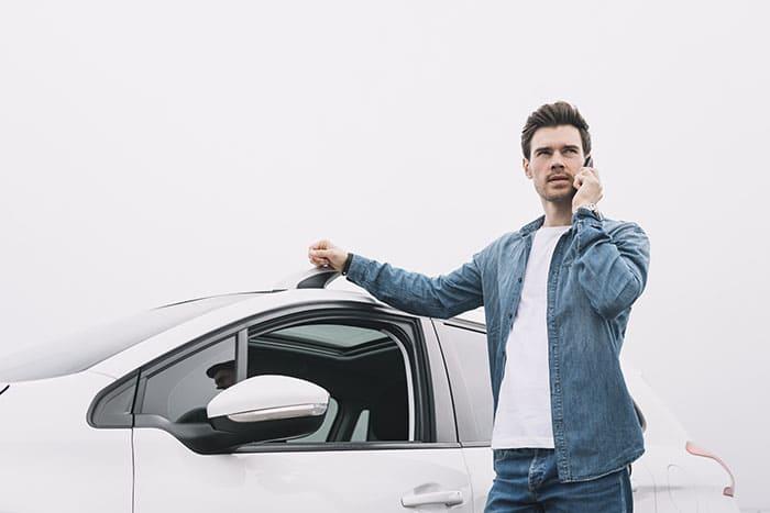 Mężczyzna dzwoni na zewnątrz auta